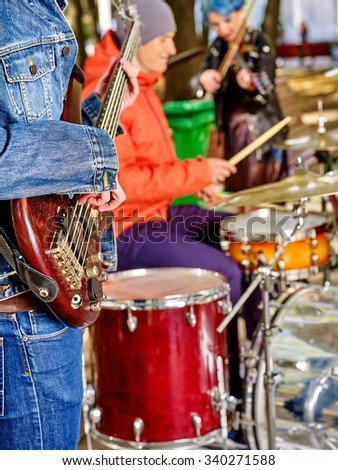 Music street performers with girl violinist on autumn outdoor. Drums in the foreground. - stock photo