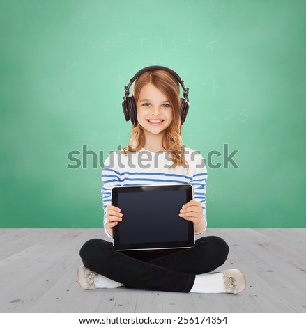 music, technology, people and childhood concept - happy girl with headphones showing tablet pc computer blank screen over green chalk board background - stock photo