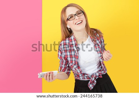 Music. Woman dancing with earbuds / headphones listening to music on smartphone. Playful happy smiling young Caucasian woman isolated on yellow pink background. - stock photo