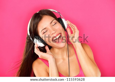 Music. Woman listening to music on headphones enjoying a dance. Closeup portrait of asian girl on pink background - stock photo