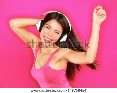 Music - woman wearing headphones dancing listening to music on mp3 player or smart phone. Fresh energetic happy multiracial Asian Chinese / Caucasian brunette dancer on pink background. - stock photo