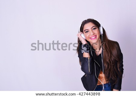 Music. Young hispanic woman listening to music with headphones. Playful smiling woman isolated over grey background. - stock photo