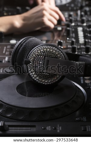 Musical clubbing professional equipment of black dj mixer console and glamour headphones with sparkles and female hand on background closeup, vertical picture - stock photo