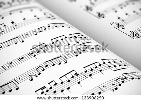 Musical concept background: macro view of white score sheet music with notes with selective focus effect - stock photo