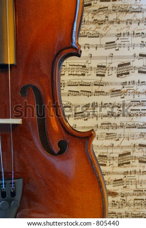 Musical Curves: The graceful curves of a violin against a musical background. - stock photo
