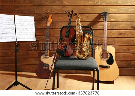 Musical instruments on a chair and note holder against wooden background - stock photo