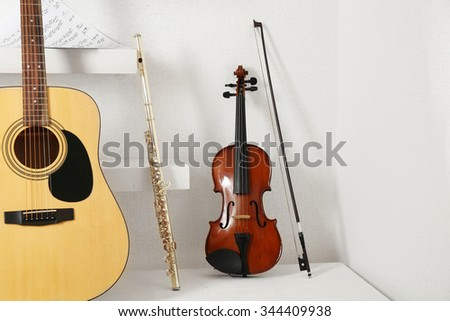 Musical instruments on decorated shelves against white wall background - stock photo