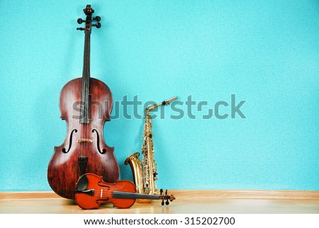 Musical instruments on turquoise wallpaper background - stock photo