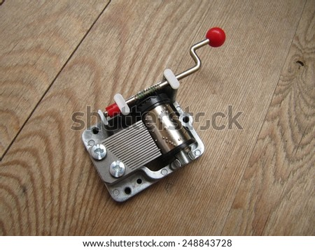 Musical machine with crank mechanism on a wooden table. - stock photo