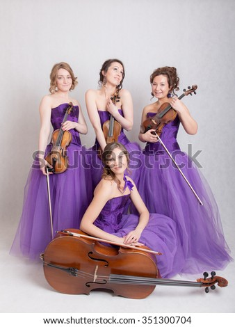 musical quartet in evening dresses with strings instruments - stock photo