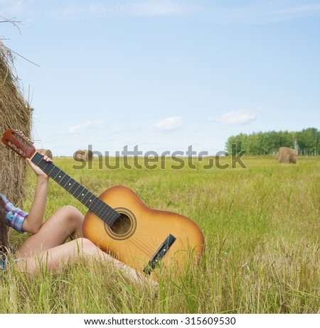 Musician Cowgirl near straw bale Alone woman on country vacations are sit on farm stack of dry thatch Nice hot summer day Young adult girl with slim sexy legs hold in hands acoustic guitar  - stock photo