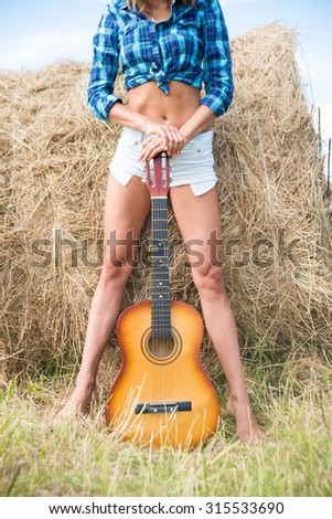 Musician Cowgirl near straw bale Alone woman on country vacations are stand on farm stack of dry thatch Nice hot summer day Young adult girl with slim sexy legs hold in hands acoustic guitar  - stock photo