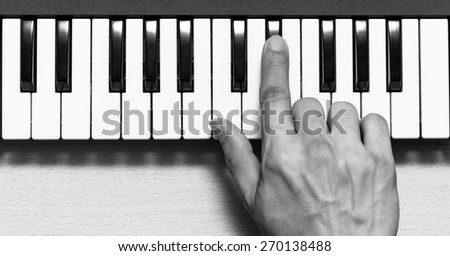 musician hand play on piano, music synthesizer keyboard / black and white processed - stock photo
