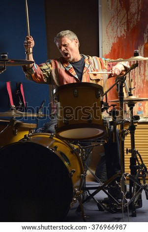 musician happy playing drums in his music Studio