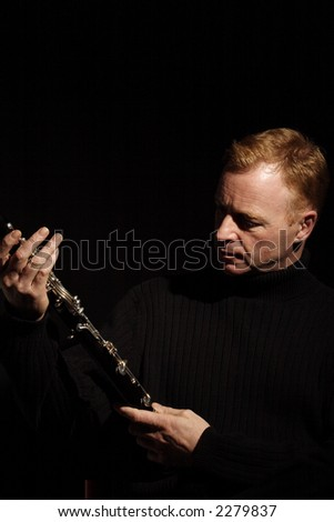 musician holding a clarinet isolated against black background - stock photo