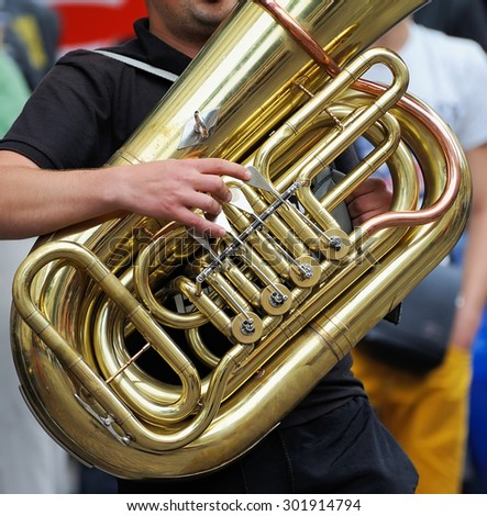 Musician is playing on the golden tuba. - stock photo