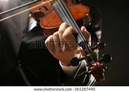 Musician play violin on black background, close up - stock photo