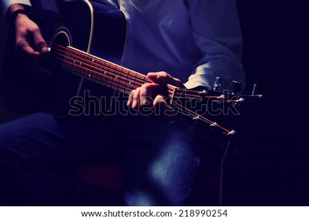 Musician playing acoustic guitar, close up, on dark background - stock photo