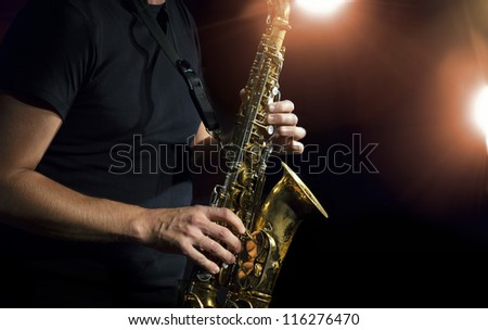 Musician playing alto saxophone on a gig. - stock photo