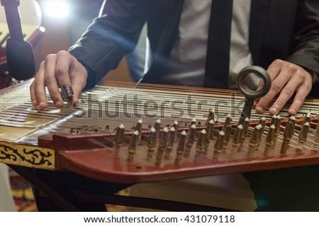 Musician Playing Arabian Qanon Musical Instrument During a Symphony - stock photo