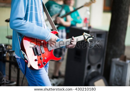 Musician playing electric guitar, close-up - stock photo