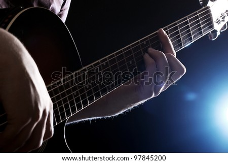 Musician playing on acoustic guitar - stock photo