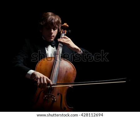musician playing the cello. Black background - stock photo