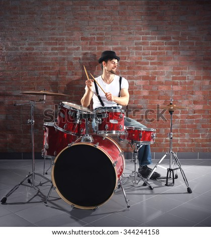 Musician playing the drums on brick wall background - stock photo