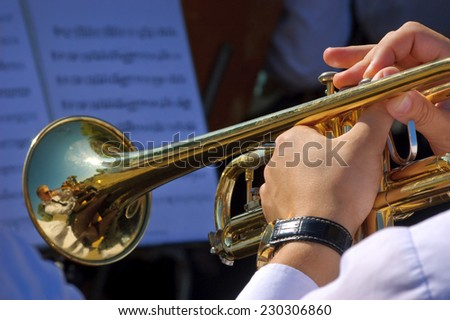 Musician playing trumpet in street orchestra - stock photo