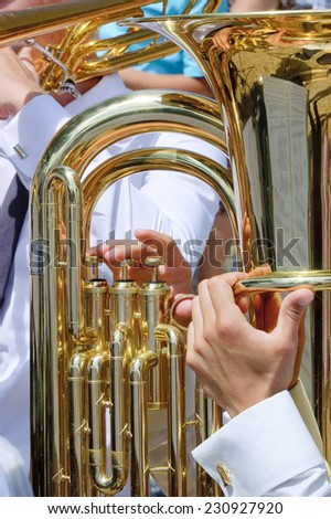 Musician playing tuba in street orchestra - stock photo