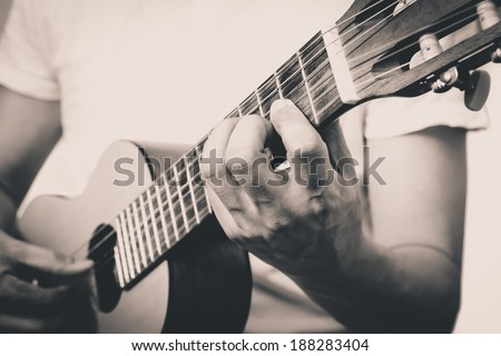 Musician plays Acoustic Guitar, B&W old film processed Vintage Photo Style - stock photo
