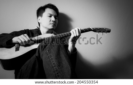 Musician plays Acoustic Guitar, B&W processed - stock photo