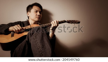 Musician plays Acoustic Guitar, sepia film processed - stock photo