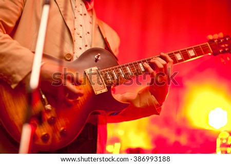 Musician plays on guitar in grey jacket.
