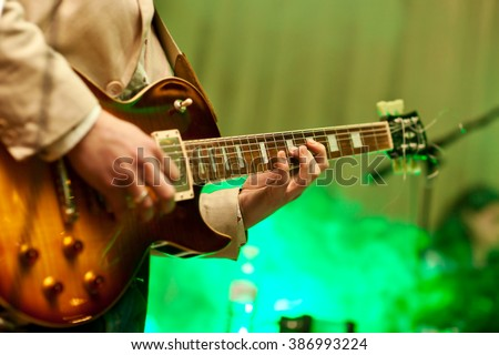 Musician plays on guitar in grey jacket. - stock photo