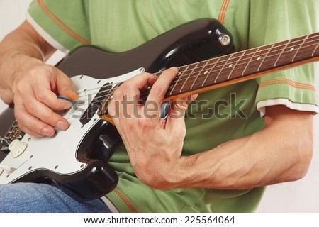 Musician put fingers for chords on electric guitar closeup - stock photo