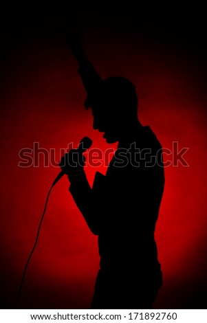 Musician silhouette on dark color background - stock photo