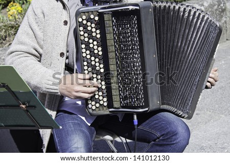 Musician with accordion playing in the street, and musical entertainment - stock photo