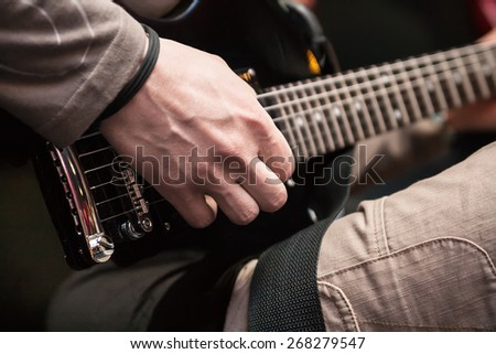 musician with guitar on black background