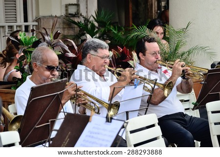 Musicians with a trumpets in an orchestra. One of the regular free performings of the brass band on the streets of Havana, Cuba, on the Central Park square, near hotel Inglaterra on May 10, 2013. - stock photo