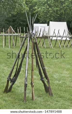 Muskets with bayonets stacked together in Union camp at reenactment of battle in American Civil War (1861-1865), Lombard, Illinois (selective focus) - stock photo