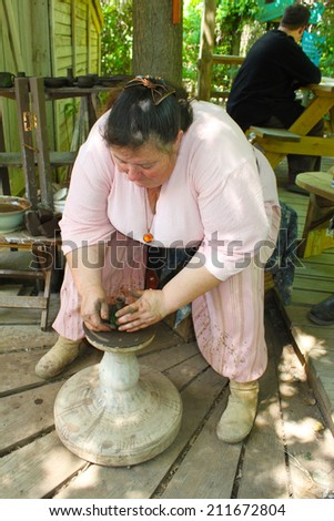 MUSKOGEE, OK - MAY 24: A potter shows of her craft on the spinning wheel at the Oklahoma 19th annual Renaissance Festival on May 24, 2014 at the Castle of Muskogee in Muskogee, OK
