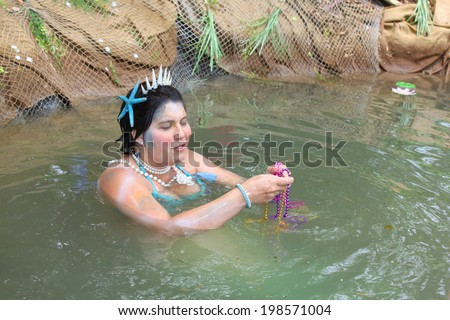 MUSKOGEE, OK - MAY 24: A woman dressed as a fairy mermaid shares treasures and smiles with kids at Oklahoma 19th annual Renaissance Festival on May 24, 2014 at the Castle of Muskogee in Muskogee, OK