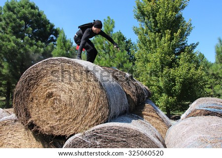 MUSKOGEE, OK - Sept. 12: Athletes jump over bails of hay to avoid bloody zombies during the Castle Zombie Run at the Castle of Muskogee in Muskogee, OK on September 12, 2015 - stock photo