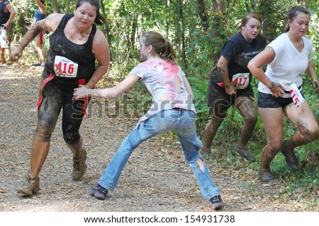 MUSKOGEE, OK - Sept. 14: Athletes try to avoid bloody zombies during the Castle Zombie Run at the Castle of Muskogee in Muskogee, OK on September 14, 2013. - stock photo