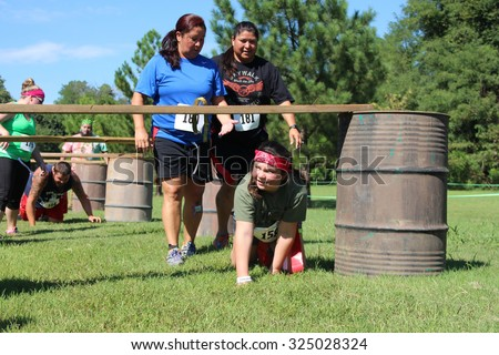 MUSKOGEE, OK - Sept. 12: Runners try to avoid bloody zombies while going through an obstacle course during the Castle Zombie Run at the Castle of Muskogee in Muskogee, OK on September 12, 2015.