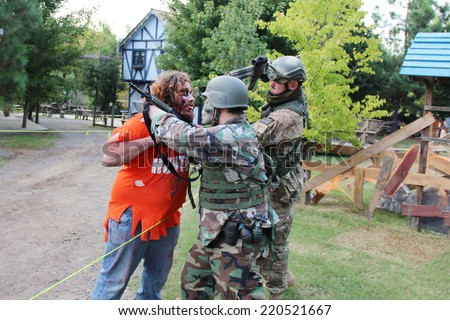 MUSKOGEE, OK - Sept. 13: Soldiers dressed in camouflage hunt zombies during the Castle Zombie Run at the Castle of Muskogee in Muskogee, OK on September 13, 2014.