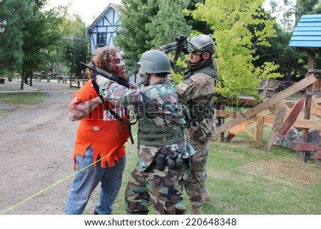 MUSKOGEE, OK - Sept. 13: Soldiers dressed in camouflage hunt zombies during the Castle Zombie Run at the Castle of Muskogee in Muskogee, OK on September 13, 2014. - stock photo