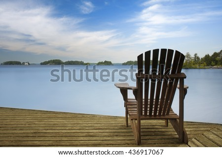 Muskoka chair facing a calm lake on a wooden dock