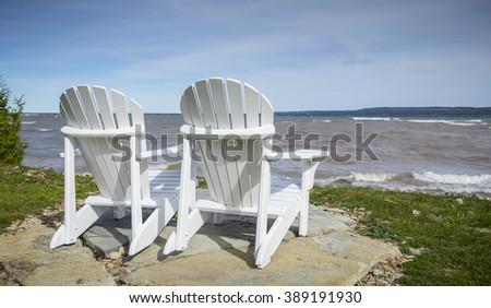 Muskoka Chairs by the water's edge for scenic view - stock photo